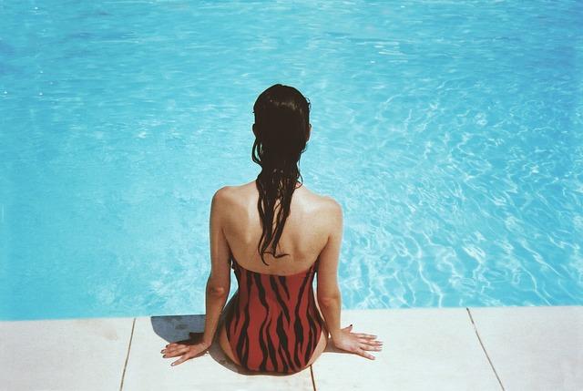 woman sitting beside pool