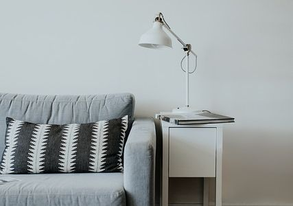 A lamp sitting on a table beside a blue couch.