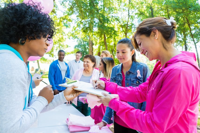 Group of diverse volunteers wearing pink and registering for an event.