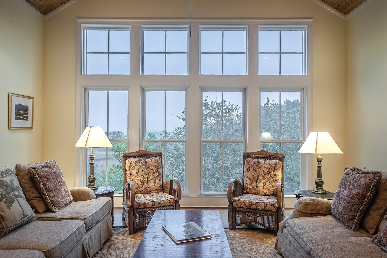 Spacious living room interior with huge windows and beige couches.