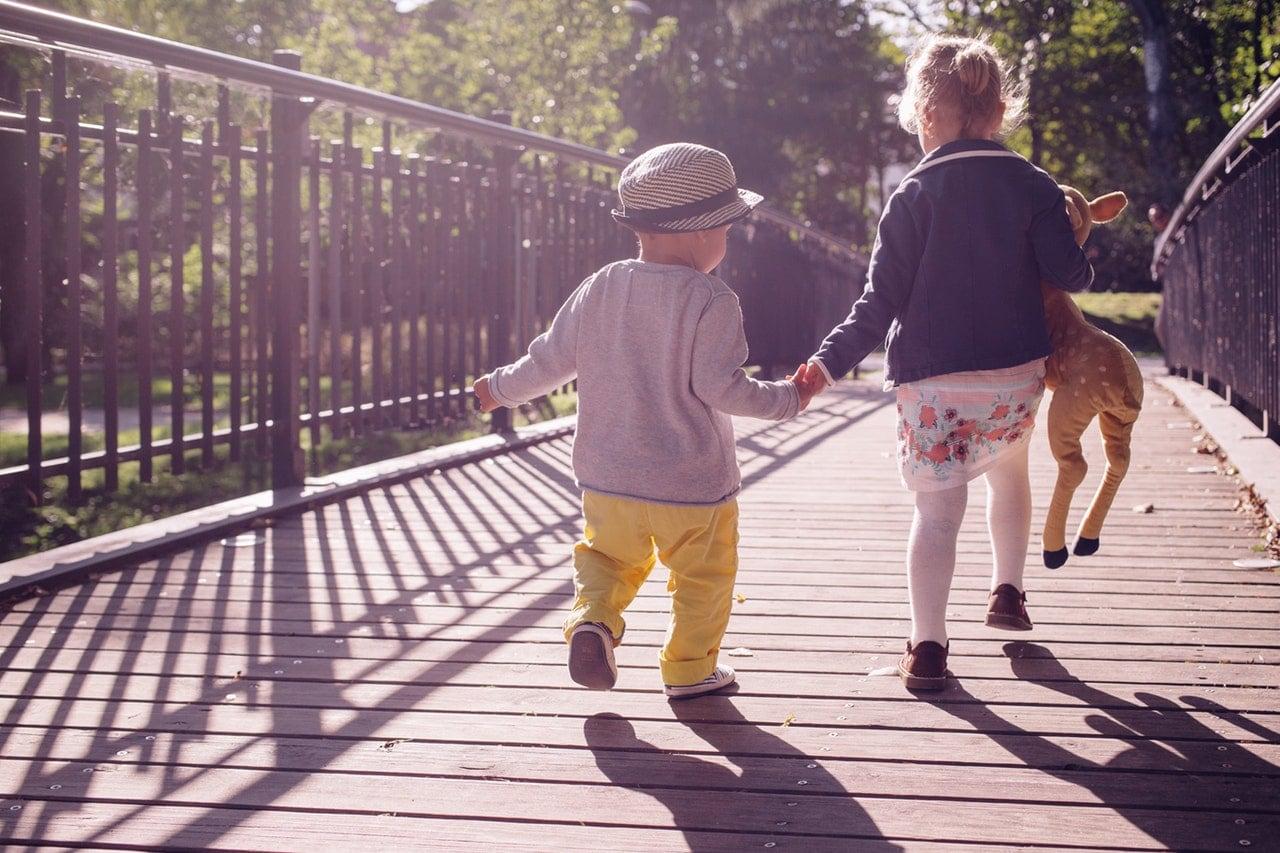 Two kids walking along a bridge path.