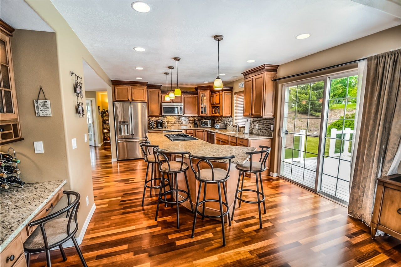 Spacious kitchen with shiny wood flooring.
