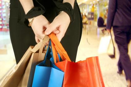 a shopper holding reusable shopping bags