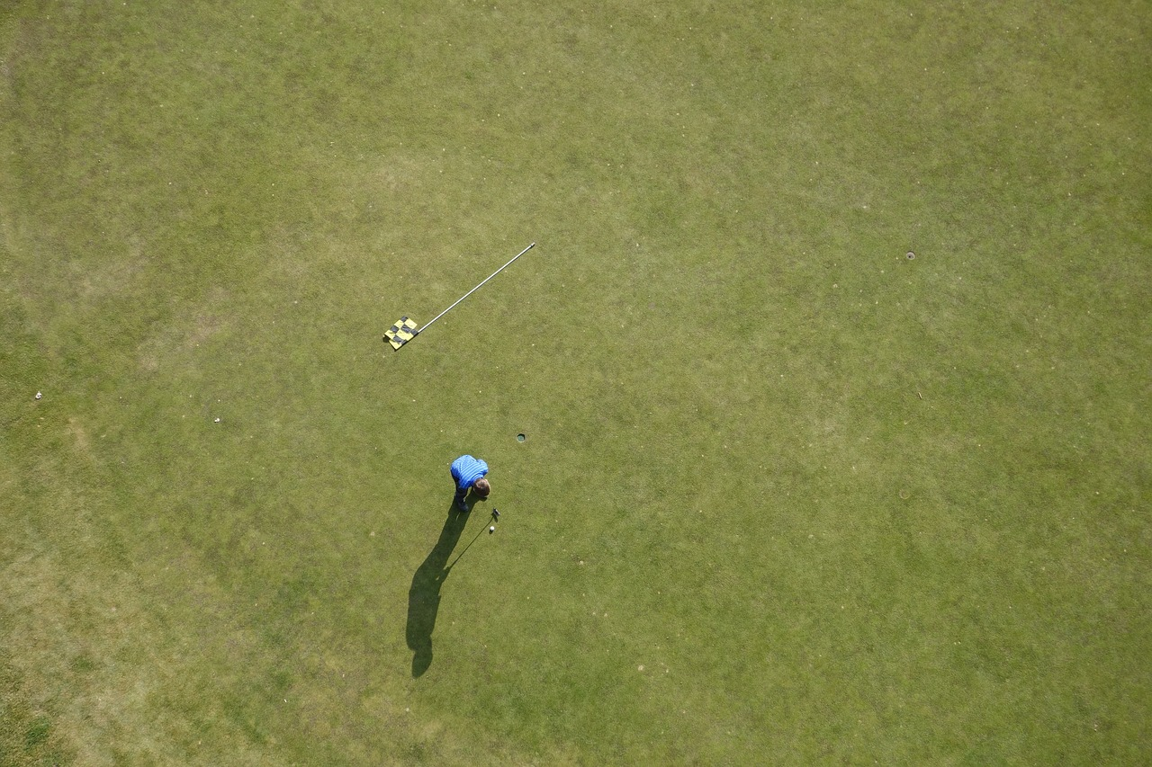 Aerial view of a man standing on a golf course ready to swing.