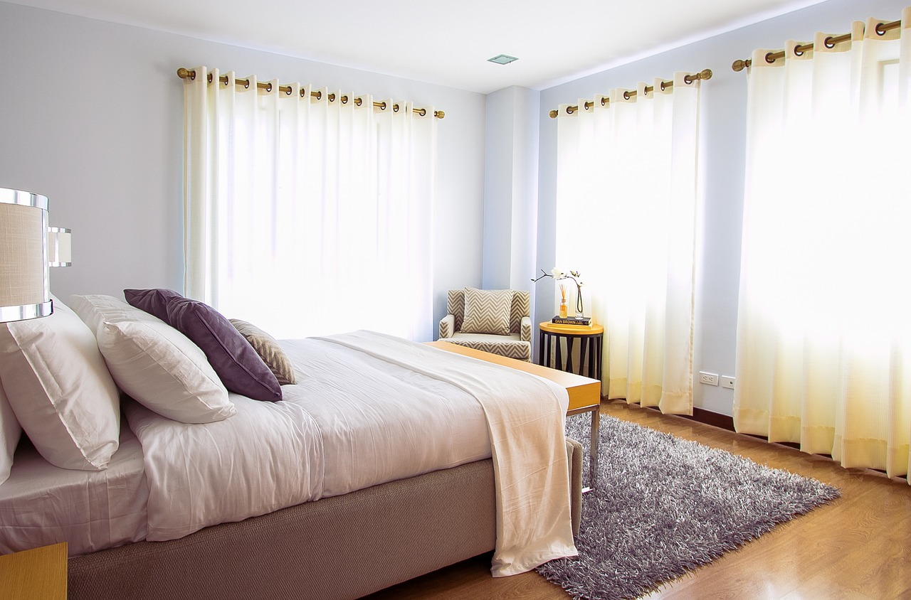 Luxurious bedroom with light yellow curtains and white bed sheets.