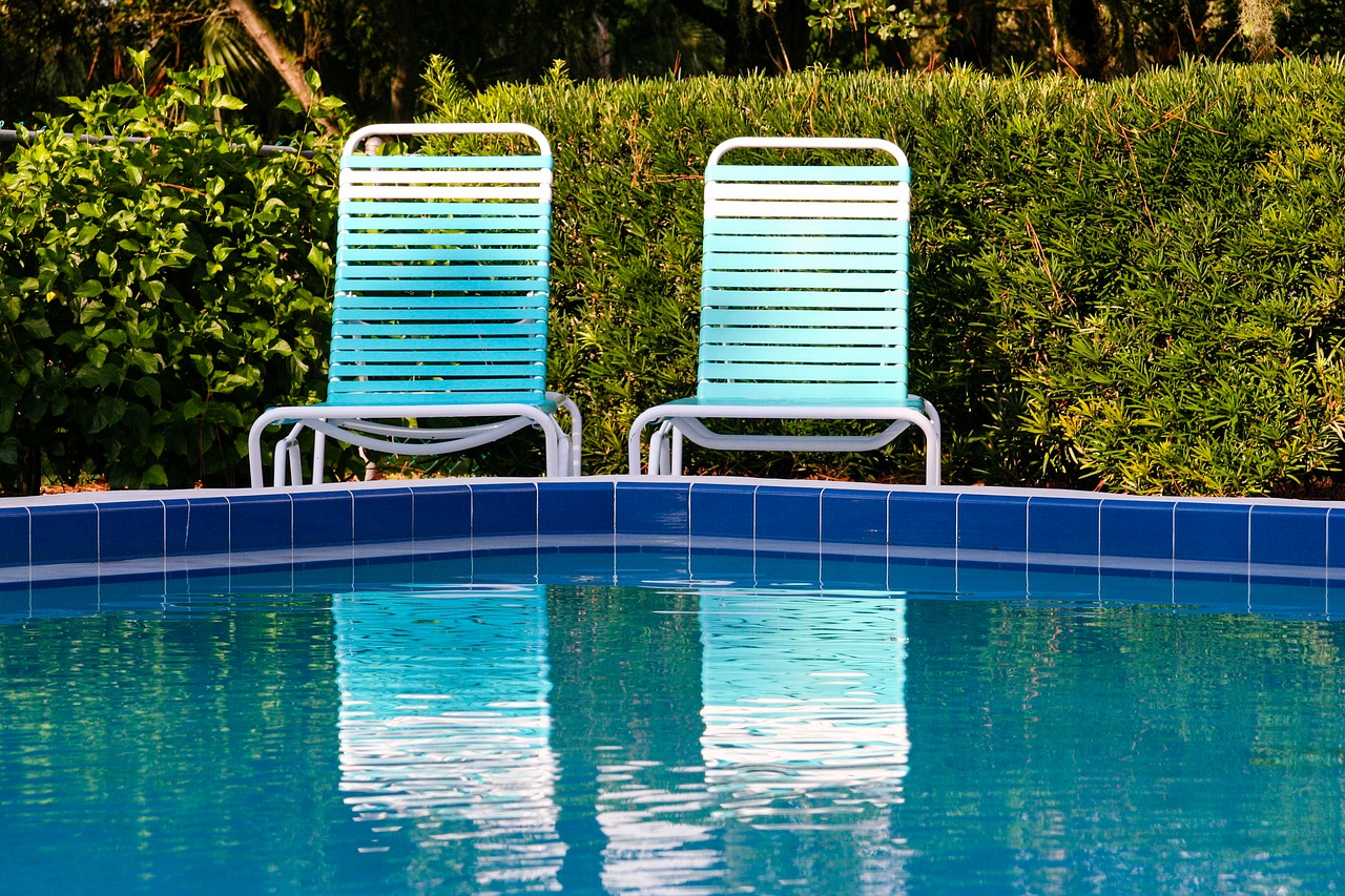 Two deck chairs sitting behind a pool.