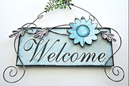 """""""welcome"""" on a sign on a home"""