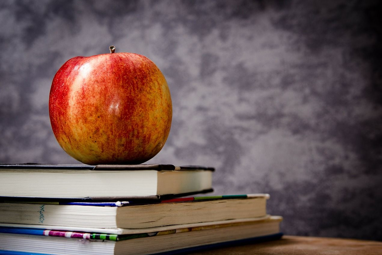 apple on a stack of books behind a classroom chalkboard