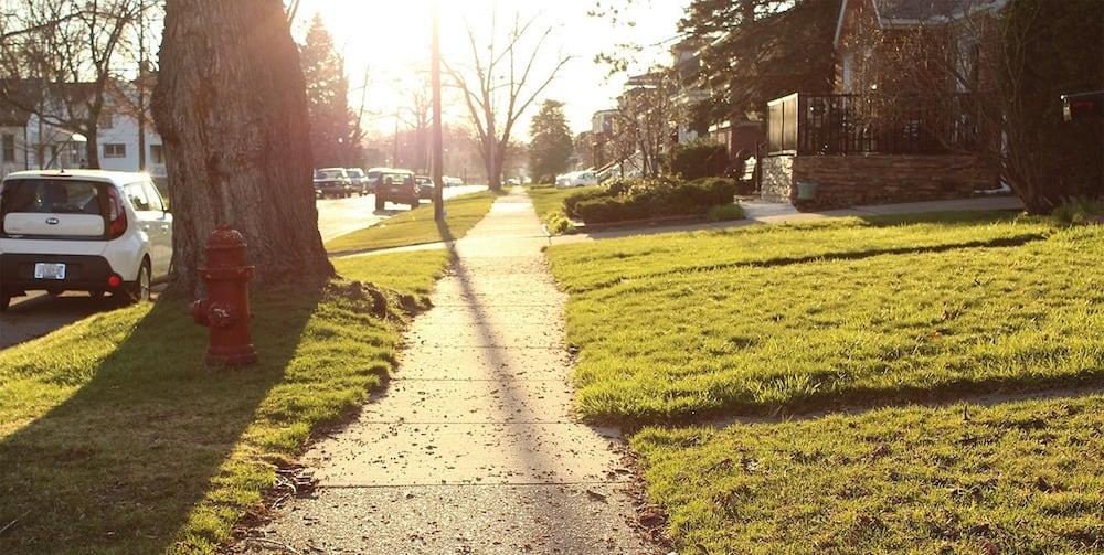 A sidewalk in a suburban neighborhood.