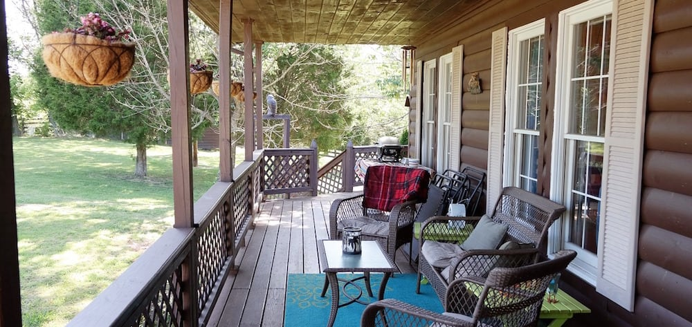 A front porch with wicker rocking chairs.
