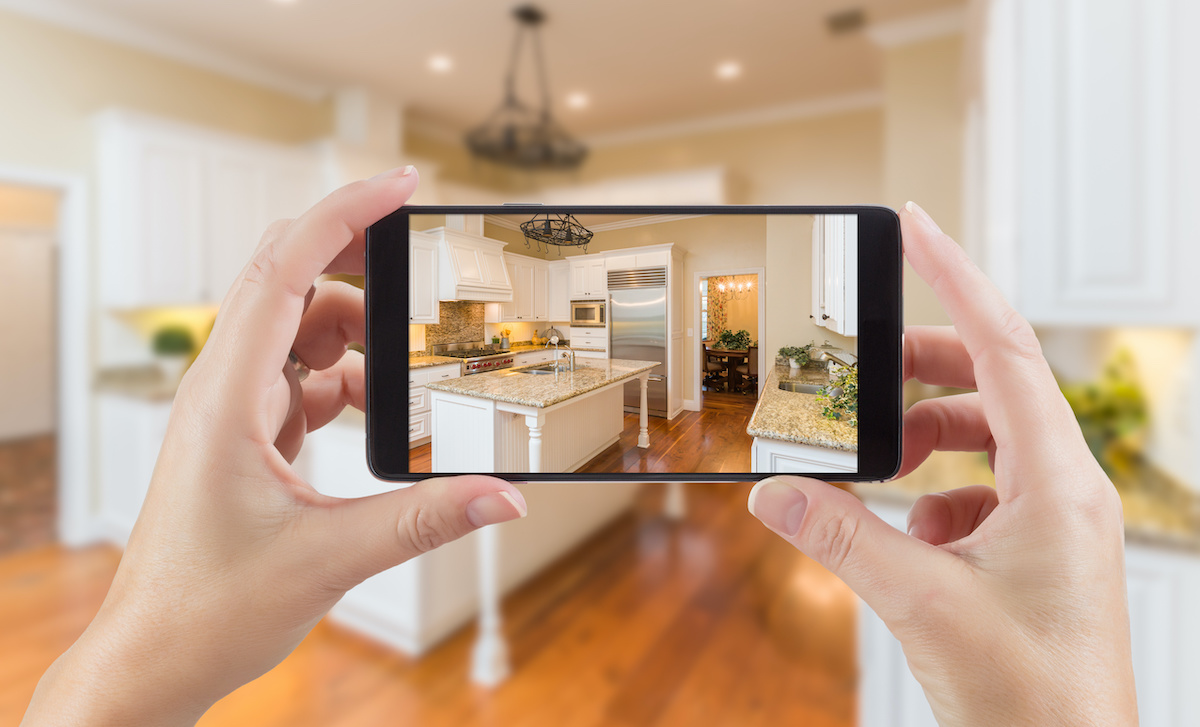 Person taking a photo of a kitchen with their mobile phone