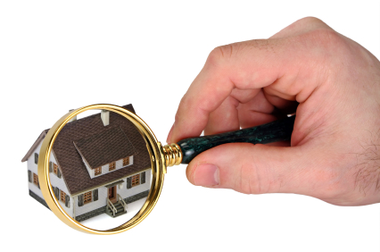 a person holding a magnifying glass over a house model
