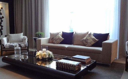 a living room with a couch and sheer curtains