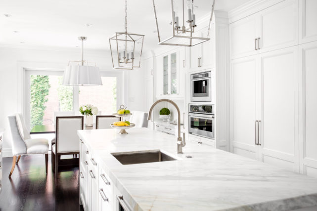 A kitchen with white counters, cabinets, and appliances.
