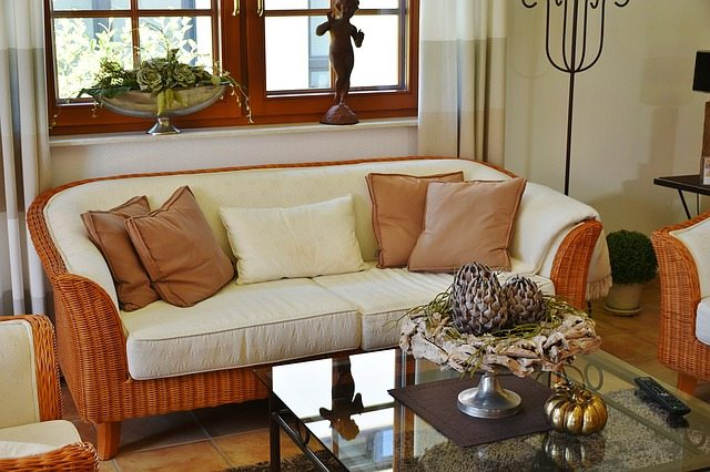 An orange wicker loveseat with cream-colored cushions.