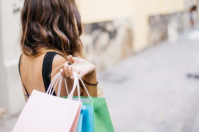 A woman holding shopping bags over her shoulder.