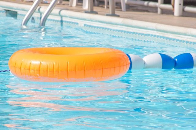 A swimming pool with an orange innertube floating on top of the water.