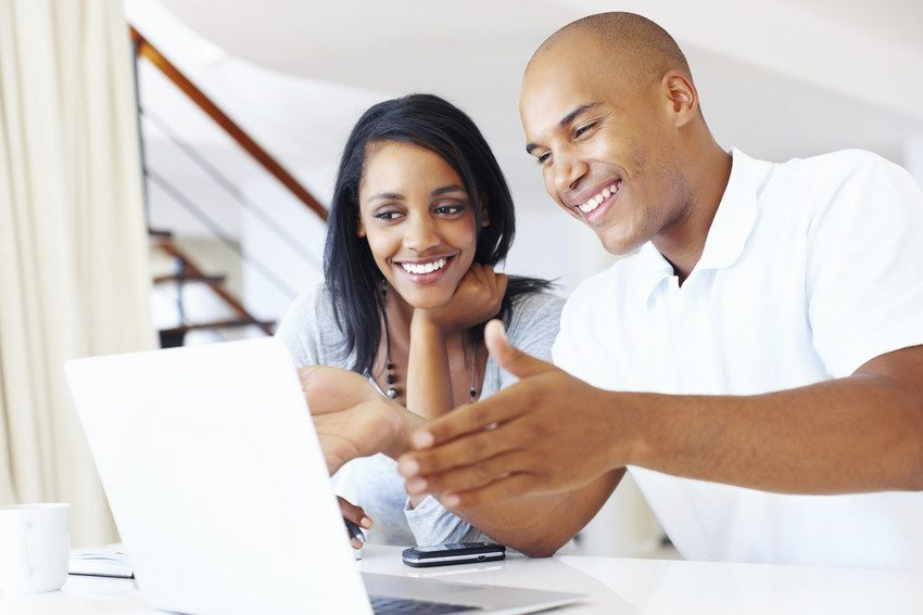 A man and woman looking at a computer and smiling.