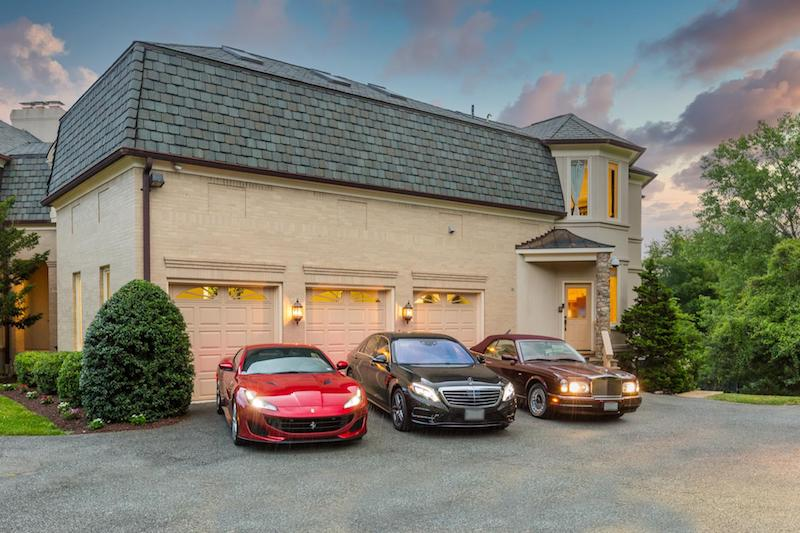 three car garage with three cars in front