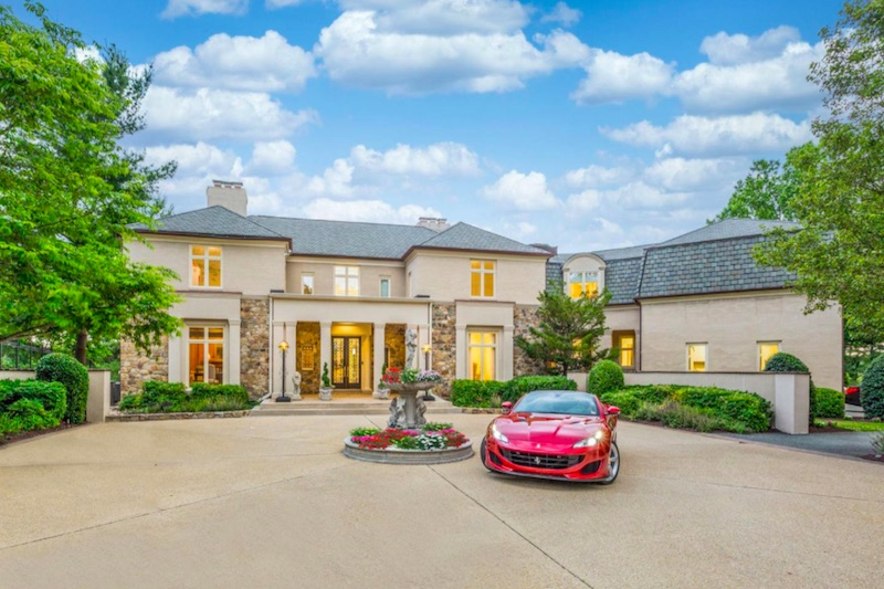 front of house with round driveway and red car
