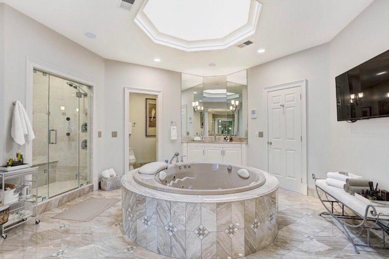 bathroom with hot tub in center
