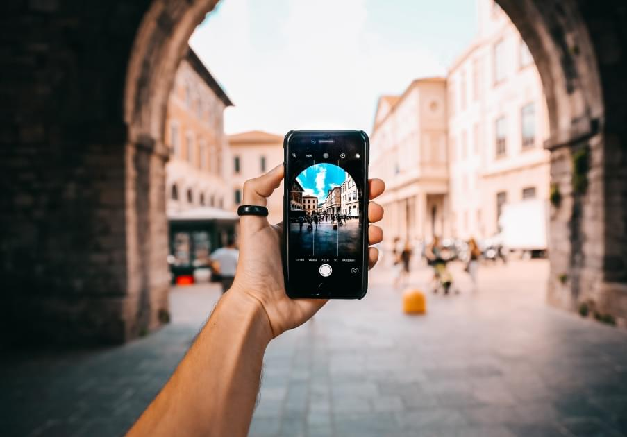 Person taking a photo of beautiful arch with phone