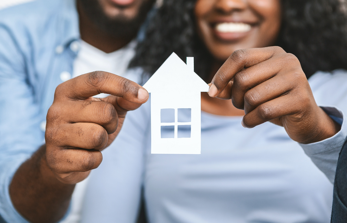 couple holding a paper house