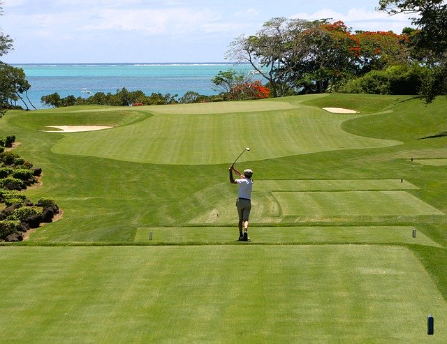 man golfing with view of the ocean