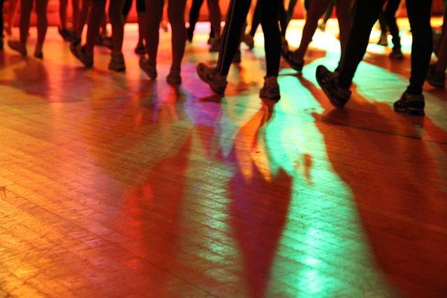 Group of adults dancing on a hardwood floor.