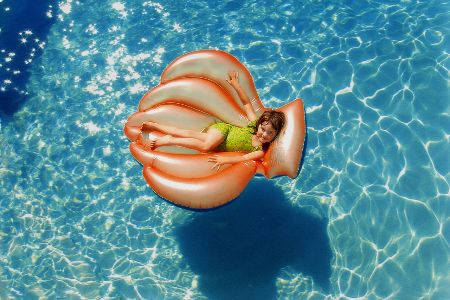 A child floating in an oversized float in a swimming pool.