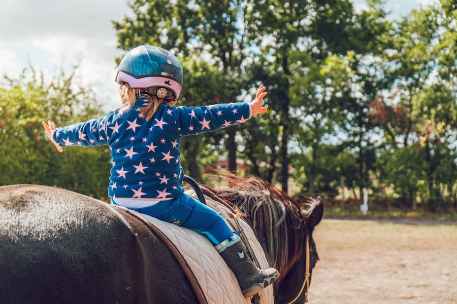 A child riding a horse with a helmet.