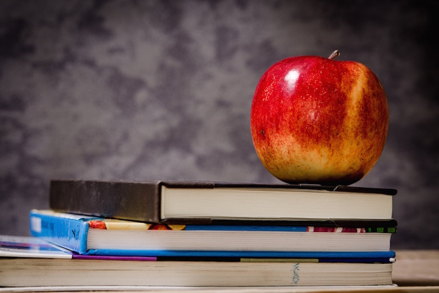 An apple on top of a stack of books.