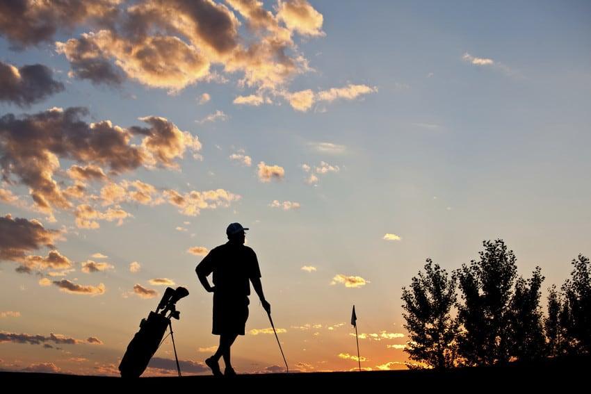 A man golfing at sunset.