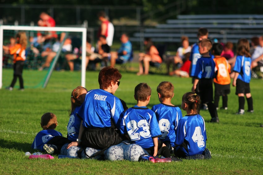 A group of school children wearing jerseys at a soccer game.