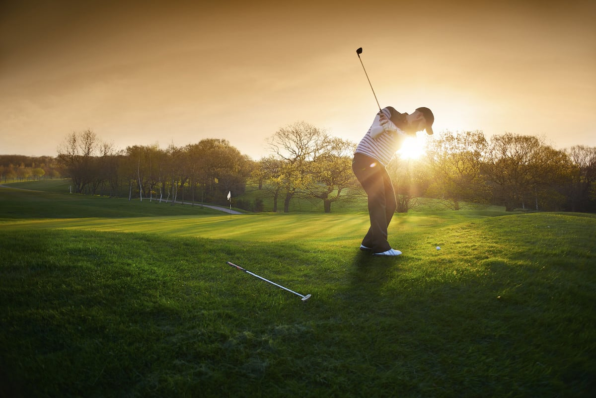 A man golfing in the sun.