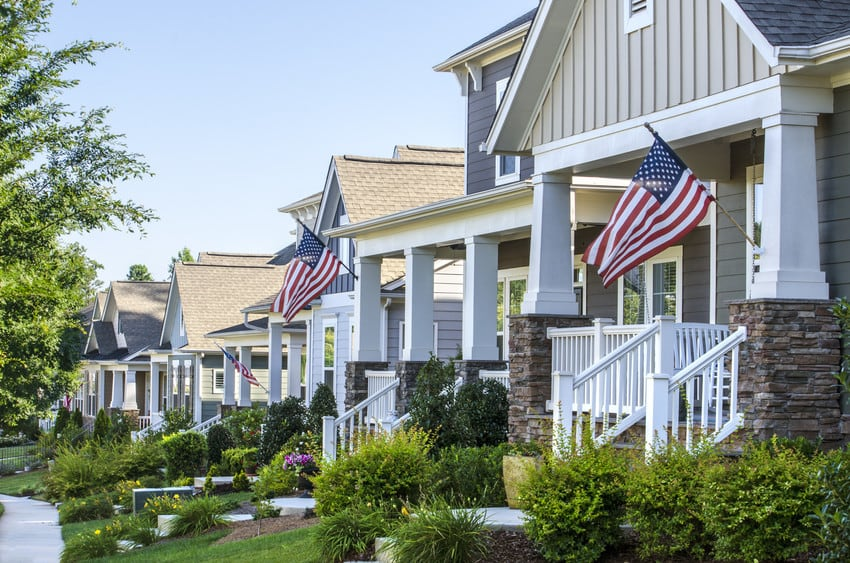 A row of suburban houses with American flags out front.
