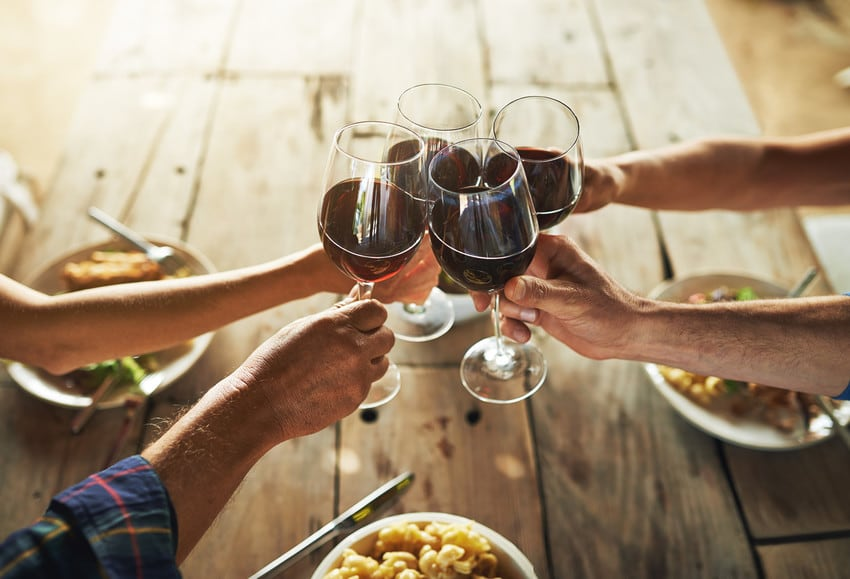 Friends drinking red wine together at a table.