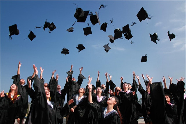 A group of high school graduates throwing their caps in the air.