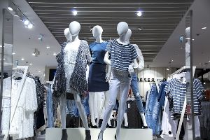 Mannequins wearing high-end women's clothes on display in a shopping mall.