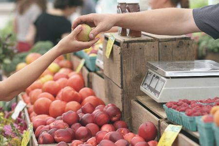 A vendor handing someone an apple from a produce stand.