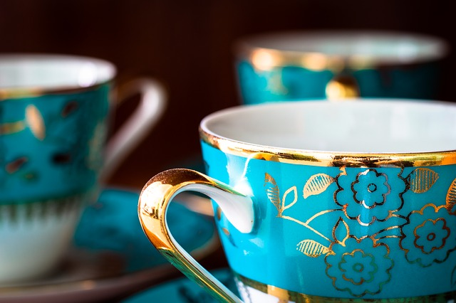 Three blue and gold vintage teacups at an antique shop.