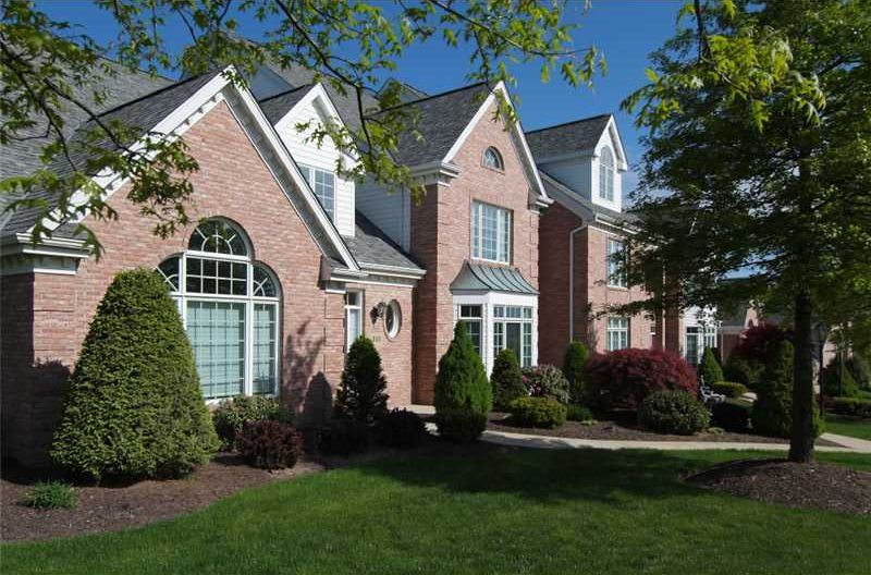 Brick villa-style townhomes and a lush green lawn.