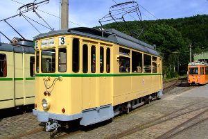 A yellow trolley car sitting on a rail.