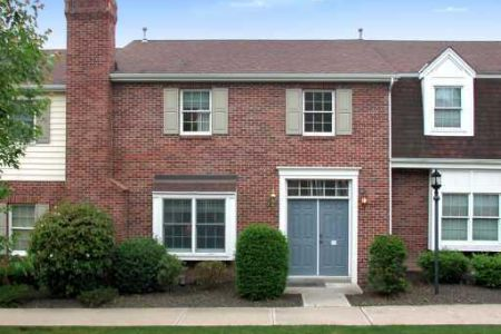 A two-story brick townhome nestled in between other brick townhomes.