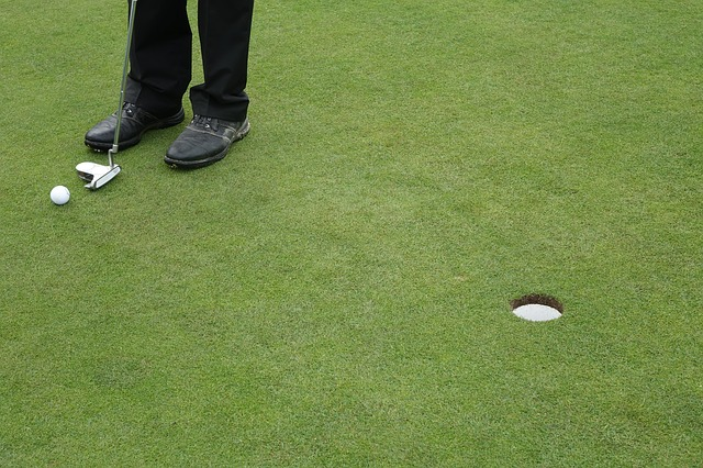 a person getting ready to put a golf ball.