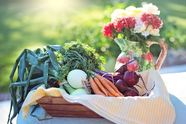 basket of local vegetables sitting beside a floral pitcher.