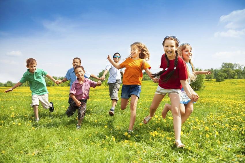 Group of kids running through a park.