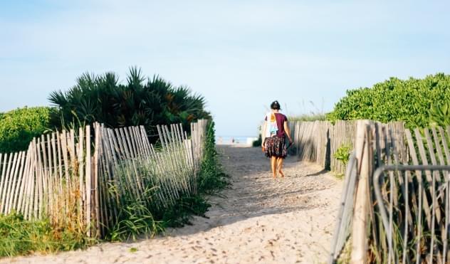 Woman walking through the sand to the beach