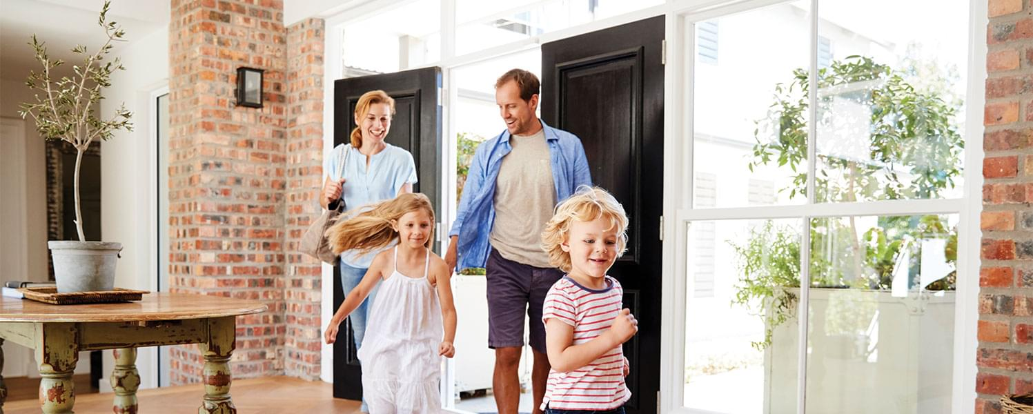 Happy family entering a sun-filled room