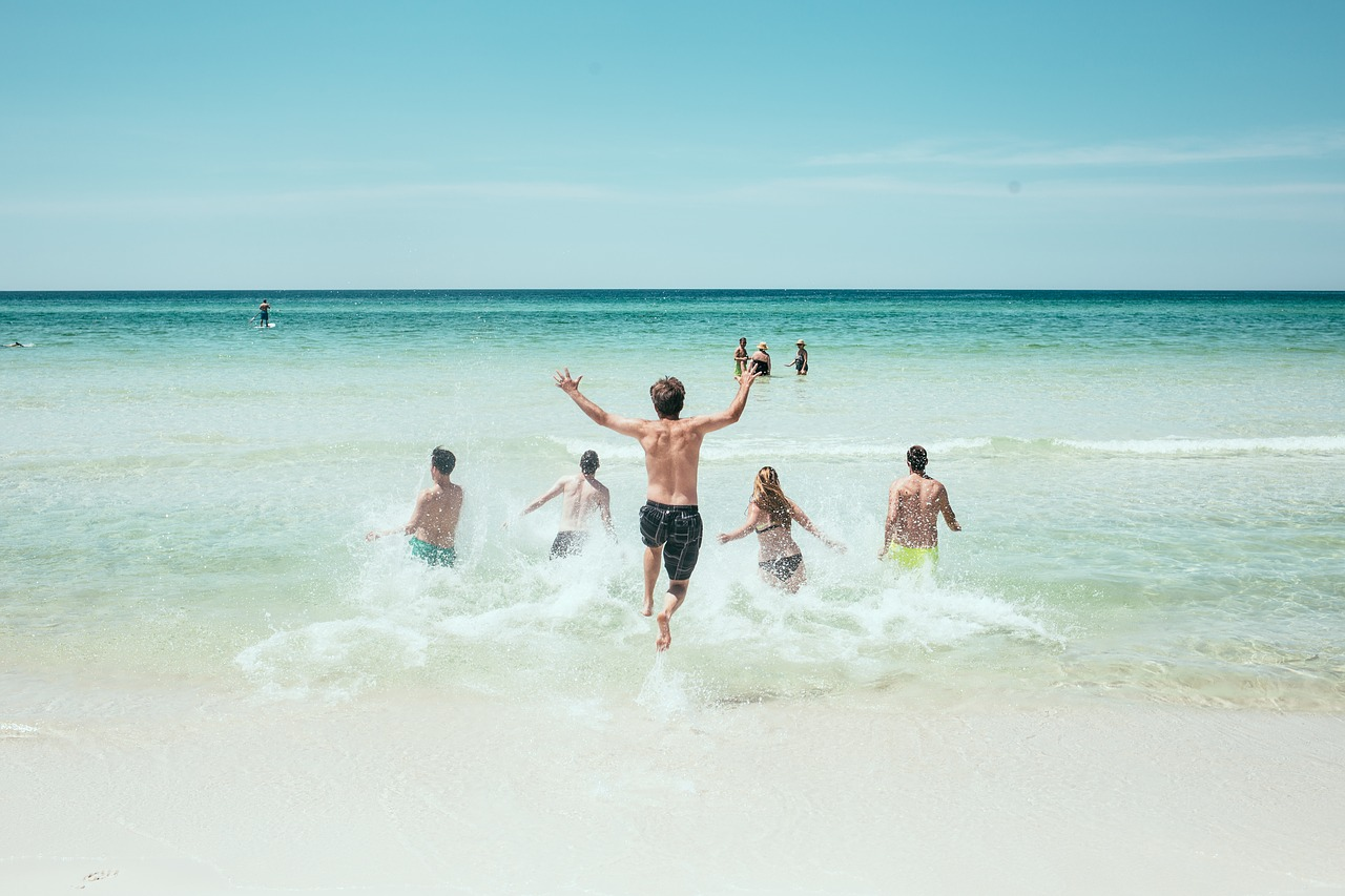 Group of young people running into the ocean.